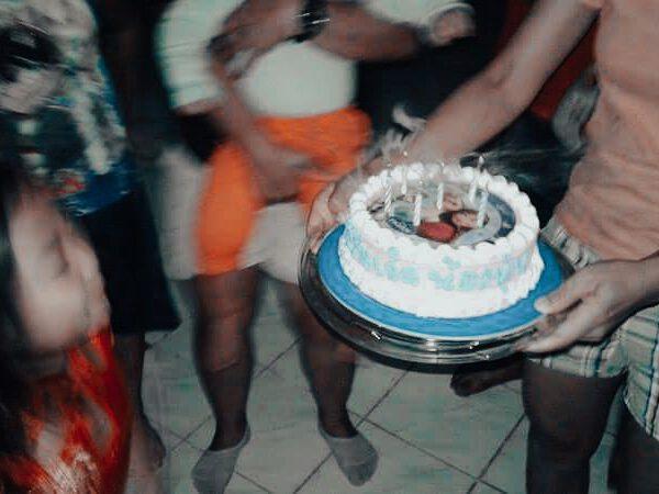 Thailändisches Mädchen bläst Geburtstagskerzen auf Kuchen aus