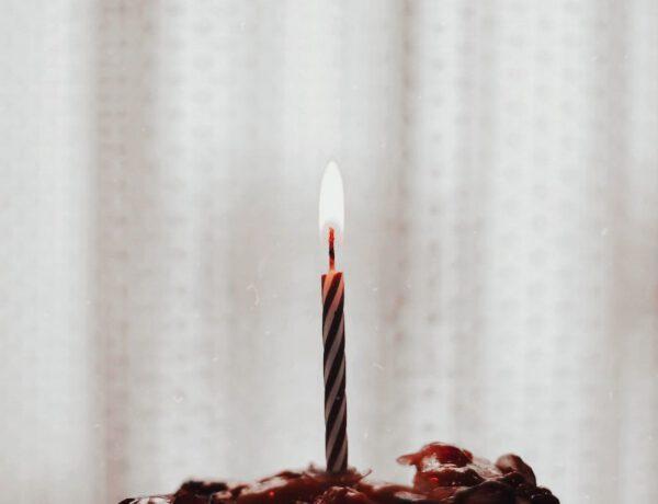 Geburtstagskerze auf einem Stück Kuchen